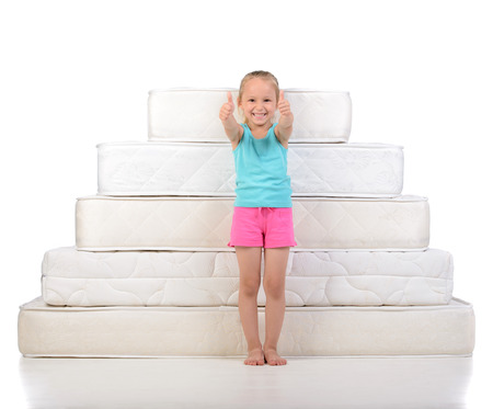 Little girl sitting on a lot of mattresses, isolated on white background photo