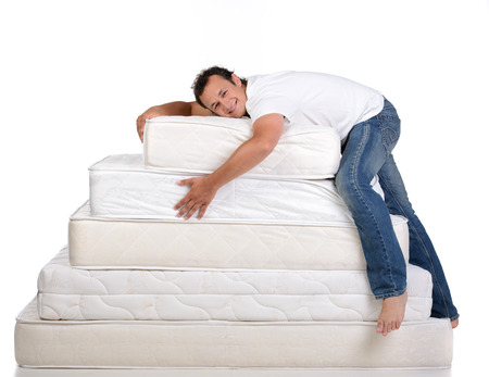 Funny man in pajamas sitting on lots of mattresses, isolated on white background