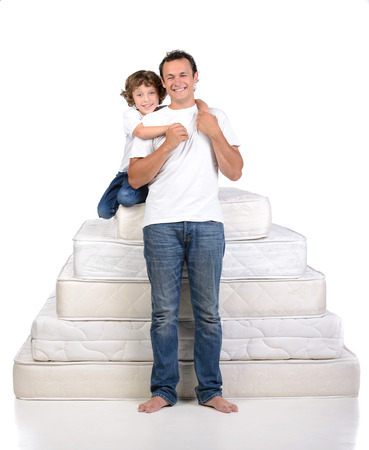 Father and little boy sitting on a large number of mattresses on white background photo