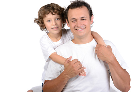Father and little boy sitting on  mattresses on white background photo