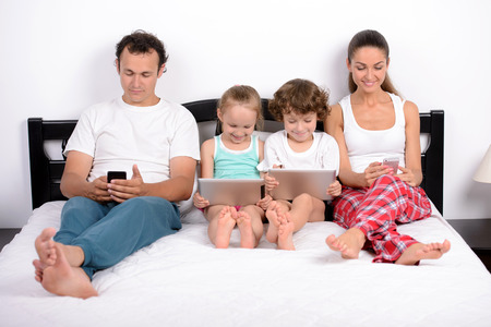 Modern technology in home. Young family, the use of tablets and phones, lying in bed at home