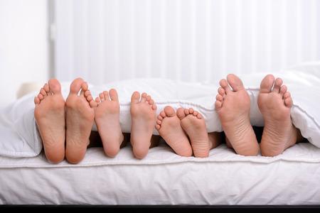 pies: Madre, padre y dos ni�os se encuentran en la cama con s�banas blancas; centran en los pies Foto de archivo