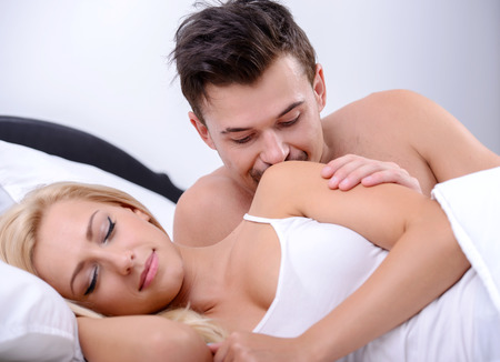 Young love couple on bed, A man looks at his wife while she is sleeping in her bedroom