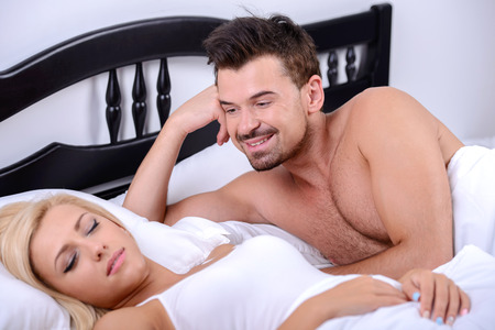 Young love couple on bed. A man looks at his wife while she is sleeping in her bedroom