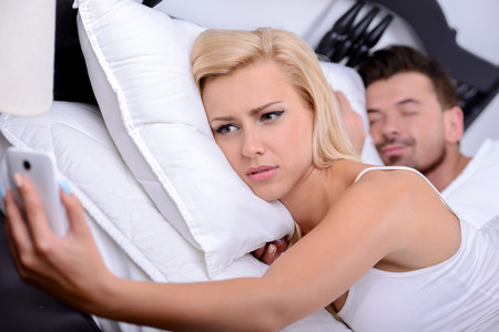 Young blonde woman, use phone in while her husband sleeps