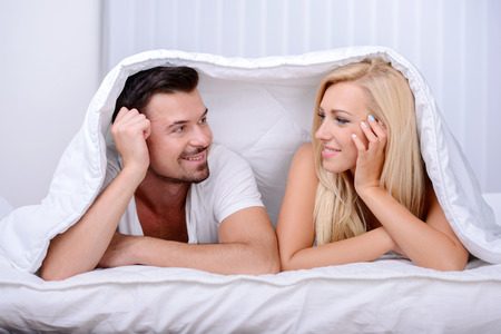 Young love couple in bed, under the blanket photo