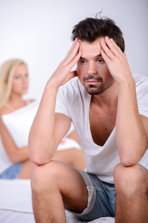 impotent: Young man sitting on the bed, against his angry wife