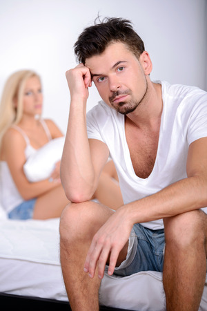 Young man sitting on the bed, against his angry wife photo