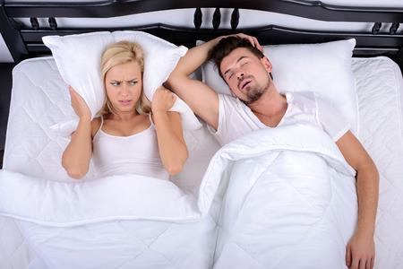 pareja durmiendo: Joven no puede dormir por los ronquidos de su marido en el dormitorio Foto de archivo