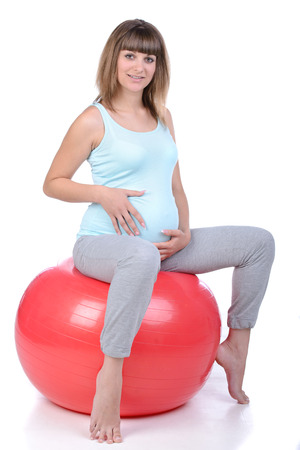 birthing: Young and healthy pregnant woman training with a fitness ball isolated on white Stock Photo