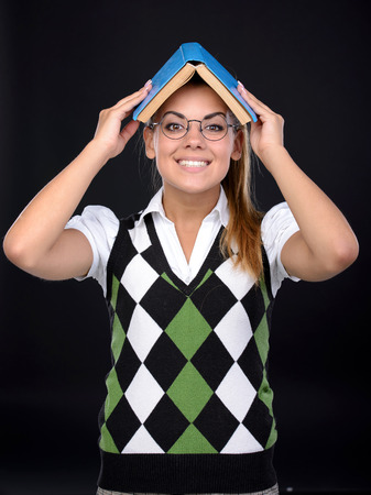 insanity: Young nerd woman crazy expression in glasses, holding book on head on black background