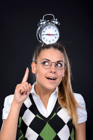 insanity: Young nerd woman crazy expression in glasses, holding an alarm clock on head on black background