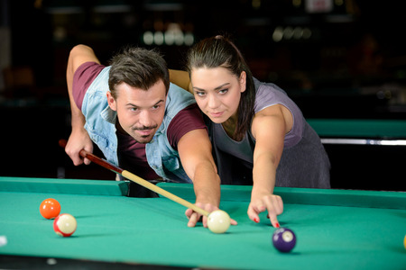 snooker hall: Young couple plays billiards in the dark billiard club