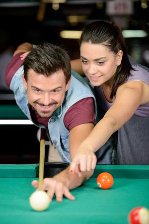 billiards hall: Young couple plays billiards in the dark billiard club