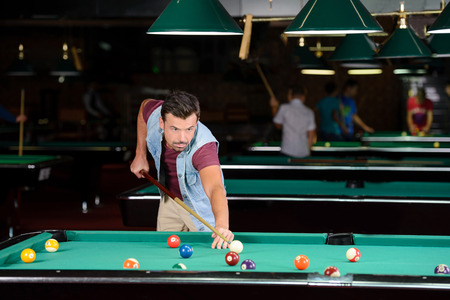 billiards halls: Young man playing billiards in the dark billiard club Stock Photo