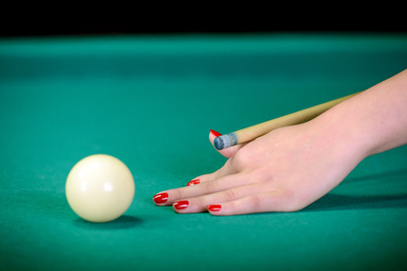 billiards halls: Billiards. Billiard balls on green table and white ball on the foreground. Hand of someone who is playing pool. Stock Photo