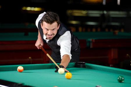 professional man: Young professional man playing billiards in the dark billiard club