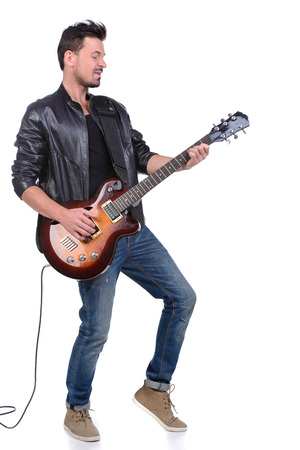 Young musician playing guitar, isolated on white Archivio Fotografico