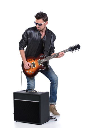 Young musician playing guitar, isolated on white photo