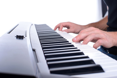 keyboard player: Male hands playing digital piano. Isolated over white background.