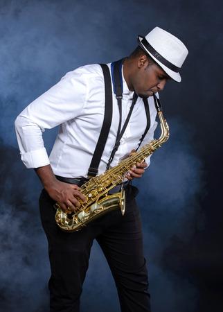 african sax: Saxophonist black men in white shirt. Smoke background