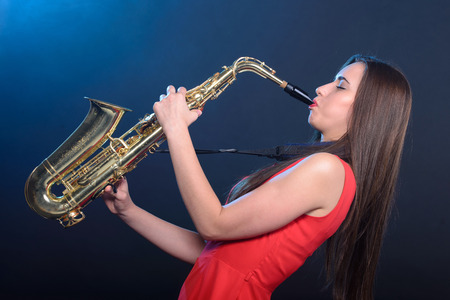 Saxophonist woman in red dress. Smoke background photo