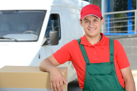 delivery van: Smiling young male postal delivery courier man in front of cargo van delivering boxes