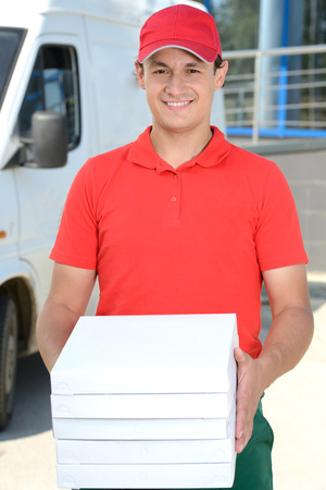 Smiling young male delivery courier man in front of cargo van delivering pizza photo