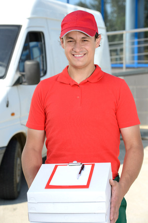 Smiling young male delivery courier man in front of cargo van delivering pizza Stock Photo