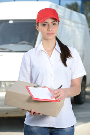 Portrait of female delivery driver with clipboard and box