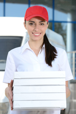 Female courier delivery pizza on background car for pizza delivery photo
