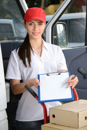 Portrait of female delivery driver with clipboard and box photo
