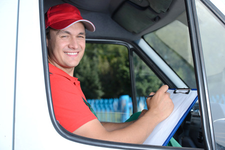 driver cap: Postal service. Delivery of a package through a delivery service Stock Photo