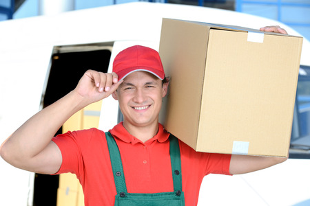 Smiling young male postal delivery courier man in front of cargo van delivering boxes photo