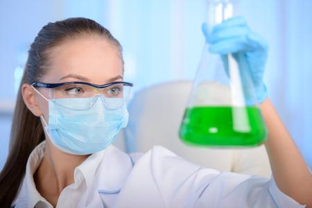 Chemist woman testing sample of liquid in laboratory photo