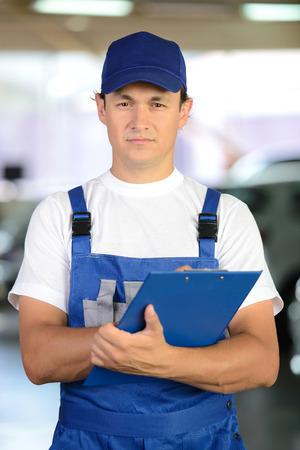 auto hoist: Auto repair service. Portrait of handsome smiling mechanic man