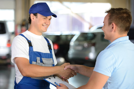 vendedores: Mecánico que da la llave del coche mientras estrechaba la mano a un cliente en un garaje