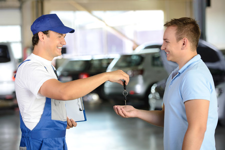 car transmission: Mechanic giving car key while shaking hand to a client in a garage
