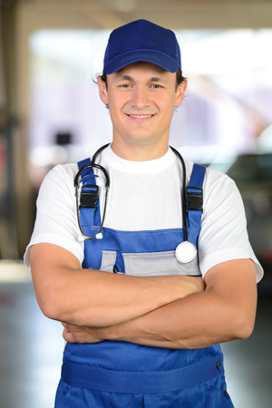 Handsome mechanic working in auto repair shop with a stethoscope around his neck. concept doctor for cars photo