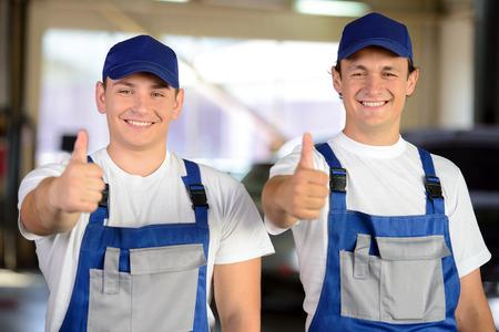 auto hoist: Portrait of two male mechanics in auto repair service Stock Photo