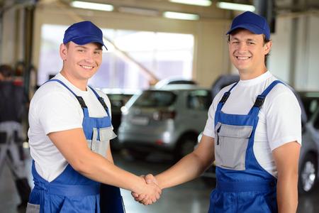 Portrait of two men handshake mechanics in auto repair service photo