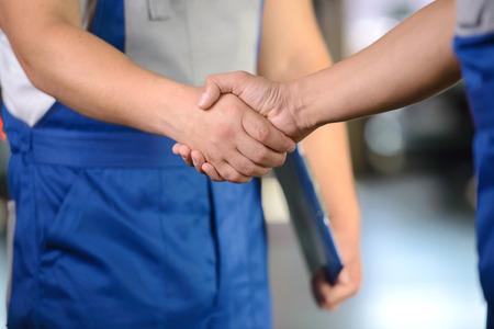 mechanic tools: Portrait of two men handshake mechanics in auto repair service