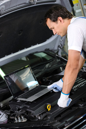 Professional mechanic using a laptop computer to check a car engine photo