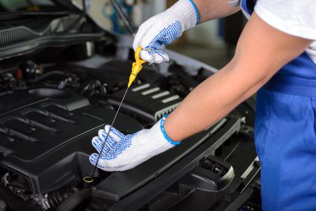 정비공 오픈 후드와 자동차에서 모터 오일을 검사의 측면보기