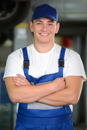 auto hoist: Portrait of confident male auto mechanic in workshop