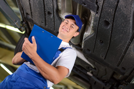 car hoist: Car mechanic examining car suspension of lifted automobile at repair service station Stock Photo