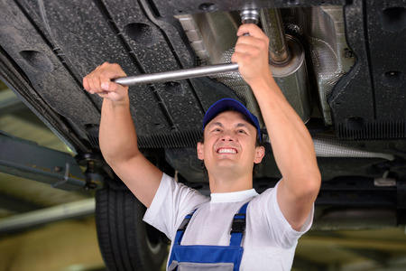 Car mechanic examining car suspension of lifted automobile at repair service station photo
