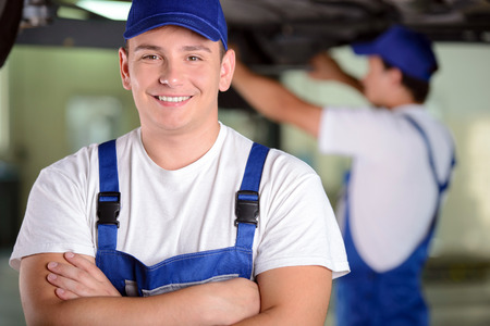 Mechanics at work shop. Confident young mechanic standing with his arms crossed and smiling at camera while another one working on the background photo