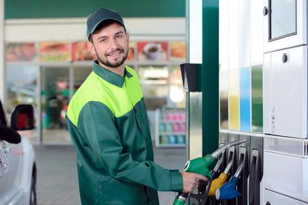 車を充填しながらガソリン スタンドでワーカーを笑顔 写真素材