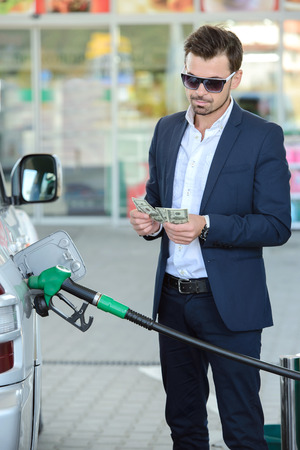 gasoil: Businessman counting money with gasoline refueling car at fuel station